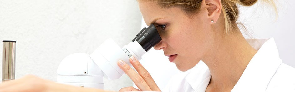 A technician looks into a microscope