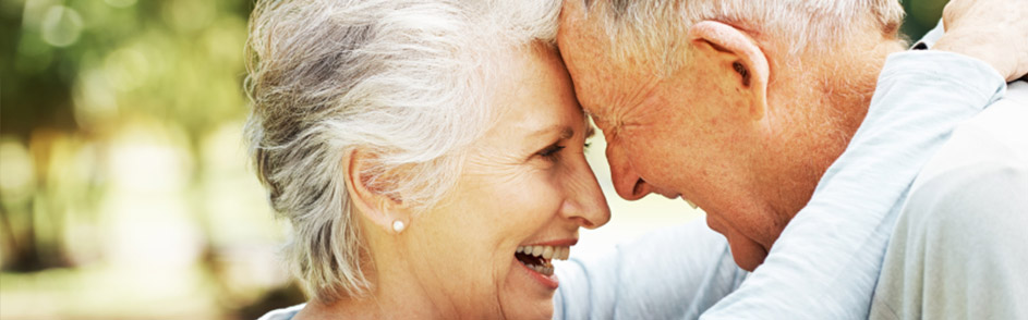An elderly couple laughing together