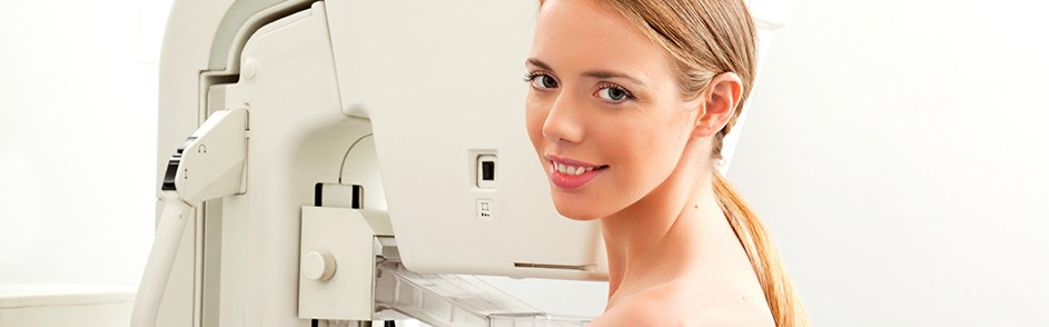 Woman smiling in front of medical machine
