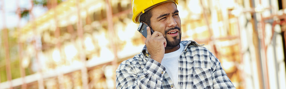 A man in a hard hat makes a phone call