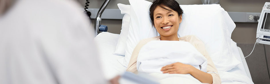 smiling woman patient in hospital bed